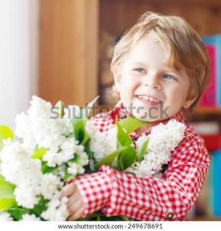 Adorable smiling little toddler boy with blooming white lilac flowers, indoor. Mother's day, father's day or valentine's day concept. - stock photo