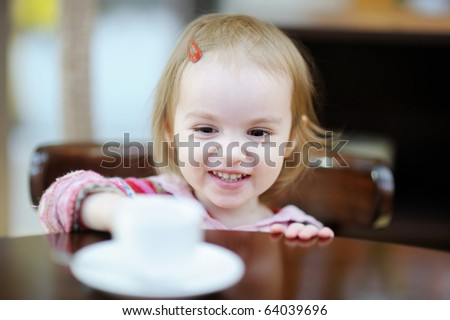 Adorable smiling toddler girl at indoor cafe
