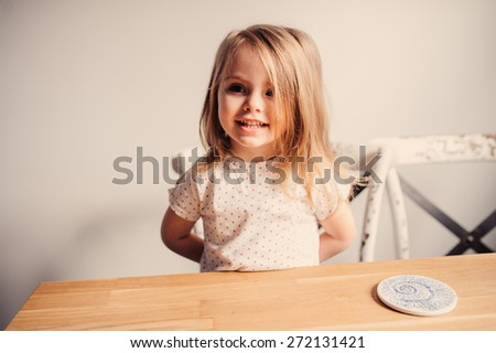 adorable smiling toddler girl having fun at home in the kitchen - stock photo