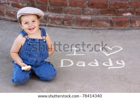 "adorable smiling toddler writing ""I love Daddy in sidewalk chalk - stock photo"