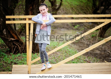 Adorable smiling tween girl in the grey hoody and skirt and colorful sneakers on the wooden small bridge - stock photo