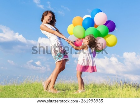 Adorable. summer holidays, celebration, family, children and people concept - mother and child with colorful balloons - stock photo