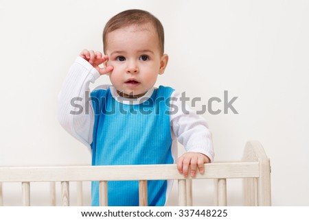 Adorable suprised baby toddler posing in the bed with hand on face on white background