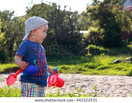 adorable surprised baby boy outdoors. photo in profile with copy space. summertime. - stock photo