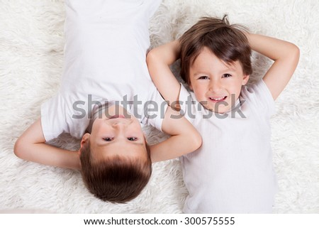 Adorable sweet happy toddler boys, brothers, lying on the ground, looking at camera, high angle view - stock photo