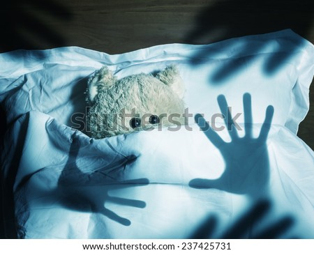 Adorable teddy bear laying in bed, scared - stock photo
