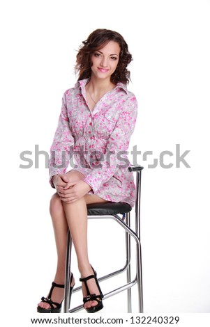 Adorable teen with a beautiful hairstyle and makeup sitting on a chair