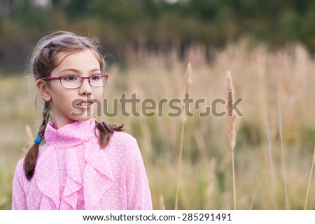 Adorable teenage girl in glasses at autumn field.  - stock photo