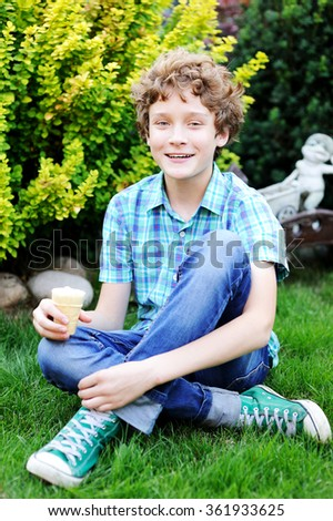 Adorable teenager boy is eating his ice cream in the garden - stock photo