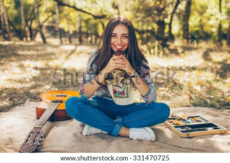 Adorable teenager girl wearing casual clothes having a picnic on autumn day in forest. Cute and beautiful hipster young woman smiling and holding a cupcake, sitting on blanket by guitar. - stock photo