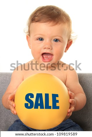 Adorable ten month old baby boy holding a yellow ball with a sale sign. Also available without text, add your own. - stock photo