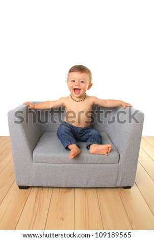 Adorable ten month old baby boy on a sofa chair. - stock photo