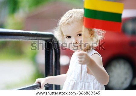 Adorable thoughtful toddler girl with Lithuanian flag - stock photo