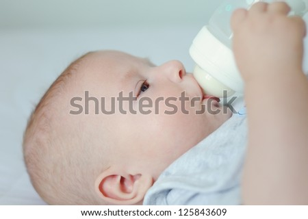 Adorable three month baby lying on a white blanket and eating milk from bottle