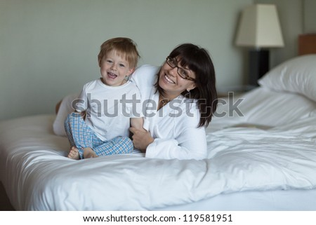 Adorable toddler and his mother in bed - stock photo