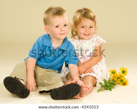 Adorable toddler baby boy and girl sit in a close embrace and the girl has bright yellow flowers the boy has just given her. Subtle cream colored background. - stock photo