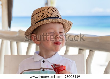 Adorable toddler boy eating delicious ice cream on a tropical beach - stock photo