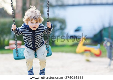 Adorable toddler boy having fun chain swing on outdoor playground. - stock photo