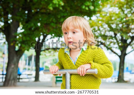 Adorable toddler boy having fun on playground, wearing bright green pullover - stock photo