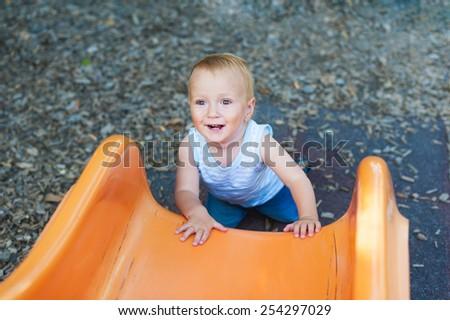 Adorable toddler boy having fun outdoors, climbing on a slide - stock photo