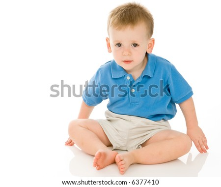 Adorable toddler boy leaning toward the viewer and making direct eye contact. Expression is one of slight incredulity or curiosity.