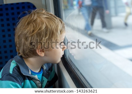 Adorable toddler boy looking out train window outside, while it moving. travel