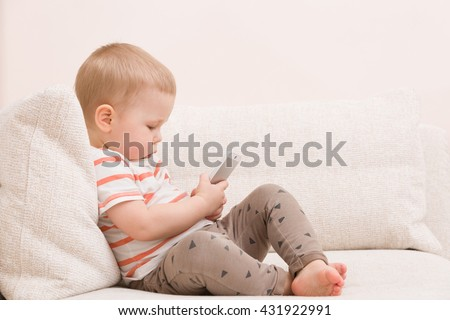 Adorable toddler boy sitting on the sofa in the living room and playing with smartphone. Child learning how to use telephone. Boy texting on the phone. - technology and lifestyle concept