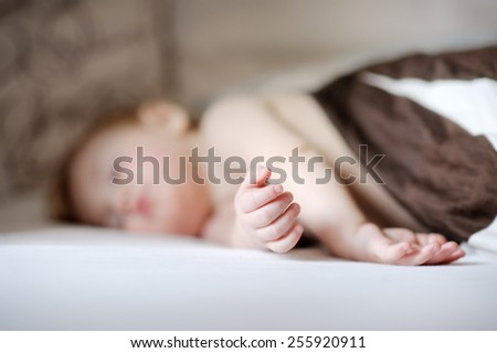 Adorable toddler boy sleeping in a bed, focus on hands - stock photo