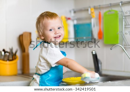 Adorable toddler child washing dishes in kitchen. Little boy having fun with helping to his mother with housework. - stock photo
