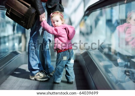 Adorable toddler girl and her father standing on moving escalator - stock photo