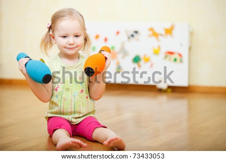 Adorable toddler girl at home holding two pins - stock photo