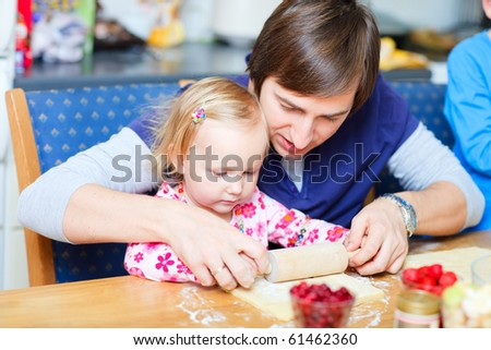 Adorable toddler girl at kitchen baking pie together with her father