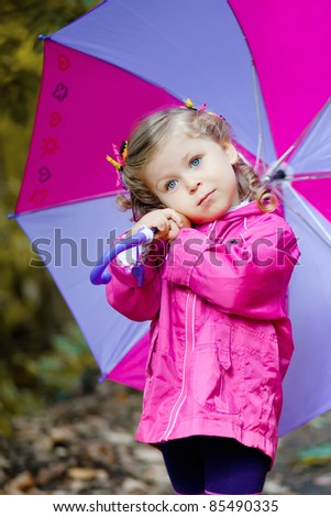 Adorable toddler girl at rainy day in autumn - stock photo