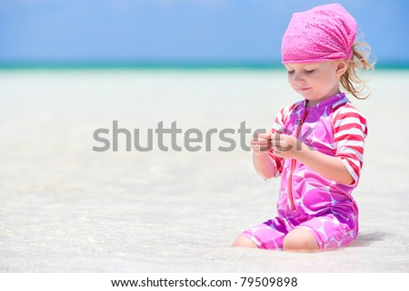 Adorable toddler girl at tropical beach playing in shallow water