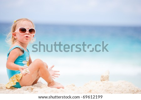 Adorable toddler girl at tropical beach playing with sand - stock photo
