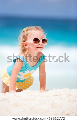 Adorable toddler girl at tropical beach playing with sand
