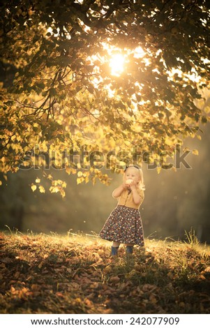 Adorable toddler girl eating an apple in the park. Autumn. Colorful leaves. Magic back light. Sunset - stock photo