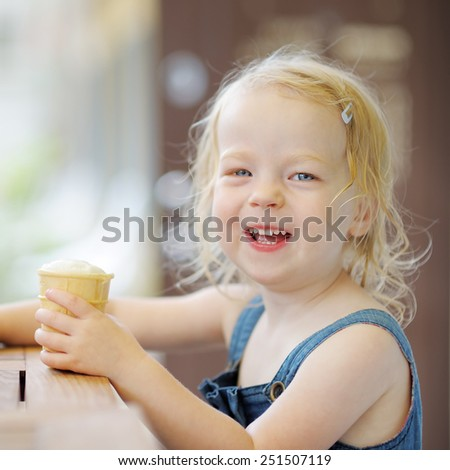 Adorable toddler girl eating ice cream in a outdoor cafe