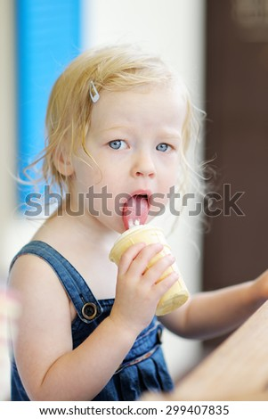 Adorable toddler girl eating ice cream in a outdoor cafe - stock photo