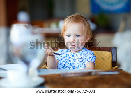 Adorable toddler girl having breakfast