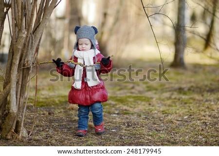 Adorable toddler girl having fun on early spring outdoors - stock photo