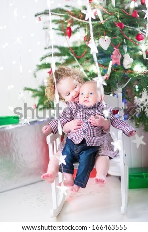 Adorable toddler girl holding her baby brother sitting in a white rocking chair under a beautiful Christmas tree - stock photo