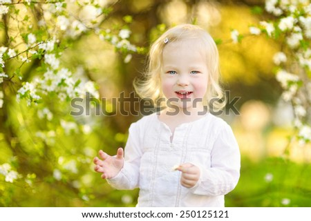 Adorable toddler girl in blooming cherry garden on beautiful spring day - stock photo