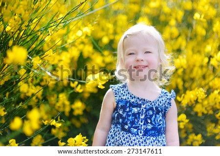 Adorable toddler girl in blooming yellow flowers on hot summer day