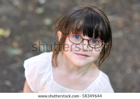 Adorable toddler girl in glasses looking to the camera - stock photo