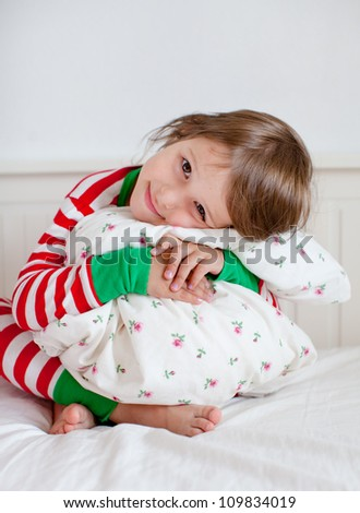 Adorable toddler girl in pajamas hugging her pillow - stock photo