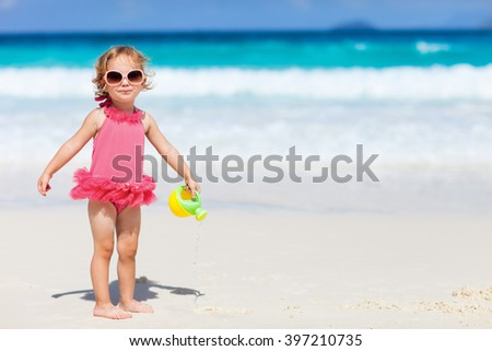 Adorable toddler girl in pink swimsuite playing with beach toys on white sand tropical beach