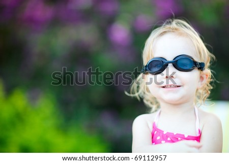 Adorable toddler girl in swimming glasses sitting near swimming pool