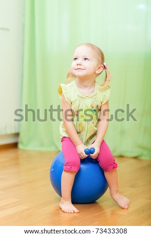 Adorable toddler girl jumping on ball in her room - stock photo