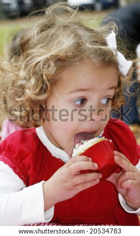 adorable toddler girl licking frosting off cupcake - stock photo